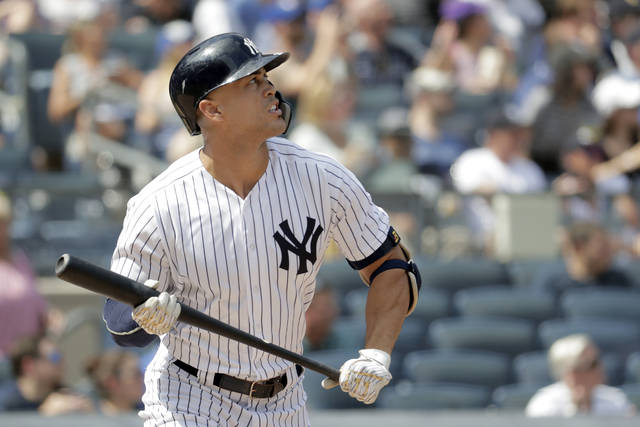 New York Yankees' Giancarlo Stanton watches his solo home run off Toronto Blue Jays starting pitcher Sean Reid-Foley during the fourth inning of a baseball game, Saturday, Aug. 18, 2018, in New York. (AP Photo/Julio Cortez)