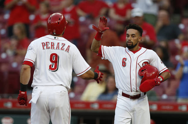 Cincinnati Reds' Jose Peraza (9) is congratulated on a two-run home run off Milwaukee Brewers starting pitcher Junior Guerra by Billy Hamilton (6) during the first inning of a baseball game, Tuesday, Aug. 28, 2018, in Cincinnati. (AP Photo/Gary Landers)