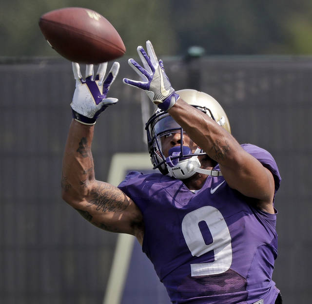 FILE - In this Aug. 10, 2018, file photo, Washington's Myles Gaskin reaches for a pass reception at NCAA college football practice, in Seattle. No. 6 Washington's potential Heisman Trophy contenders Gaskin and quarterback Jake Browning play against No. 9 Auburn in the only opening-week game between top ten teams. (AP Photo/Elaine Thompson, File)