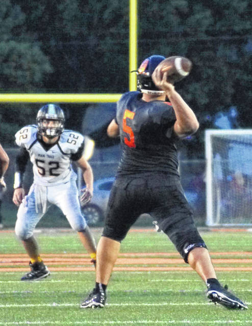 Wilmington quarterback Brady Evans unleashes a long pass that resulted in a touchdown to Cam Coomer late in the first half of Friday night's 38-7 win over Miami Trace.