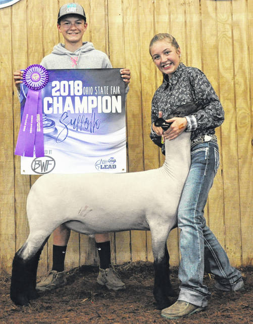 Jordan Collom of New Vienna, right, exhibited the Champion Suffolk Market Lamb at the Ohio State Fair. She is a daughter of Walter and Angie Collom. Jordan belongs to the Final Drive 4-H Club. Gene Winn of New Mexico judged the competition. Shroyer Show Stock and OSIA LEAD Council Booster Banner Program purchased the lamb for $975 at the state fair's market lamb sale.