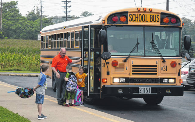 Wilmington City Schools' Business Director Curt Bone assists children in getting off their school bus Friday morning to start another school day at Holmes Elementary in Wilmington.