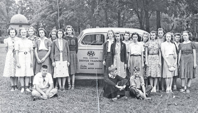 """Here's another photo we stumbled upon of the Ohio State Highway Patrol's first driving class, in July 1939; we ran another photo of the group recently, but very few of those pictured were identified. Listed on the back of this photo, the girls are, """"left to right, Emily Hiatt; Betty Snider; ??? Thompson; Martha Hodson; ???; Marilyn Martin; Dorothy Thompson; Ruth Anna Boyd; Martha Jo Starbuck; ???; Virginia Vander Voort; Annabelle Parker; Avonelle Dome; Virginia Thompson; Glenndora Ralston; and Margaret Lowery. The boys are John Frazier; Junior Harner; and Maynard Martin."""