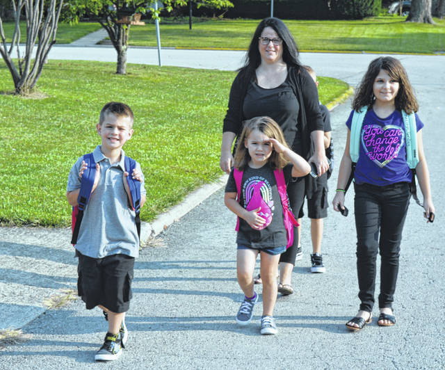 Mother Amanda Gordley accompanies four of her children Wednesday morning down Piedmont Street in Wilmington toward Holmes Elementary School. The children from left are Andrew, 7, Adriana, 6, Kerstyn, 9, and mostly hidden behind Amanda, Elijah, 8, who was not wanting to go to school, mom said. Amanda said she is excited for them as they start a new school year.