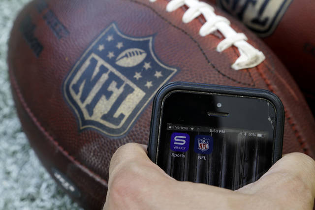 In this Thursday, Aug. 30, 2018, photo apps for NFL and Yahoo Sports are displayed on a phone on the sidelines before a preseason NFL football game between the Philadelphia Eagles and the New York Jets in Philadelphia. As the regular season starts Thursday, Sept. 6, the league is finally dropping a requirement that viewers sign in with a cable or satellite subscription, as it seeks to expand its online audience at a time when TV ratings are declining. The subscription-free games will be available on the NFL app and the Verizon-owned Yahoo Sports, Tumblr and AOL apps.  (AP Photo/Matt Rourke)