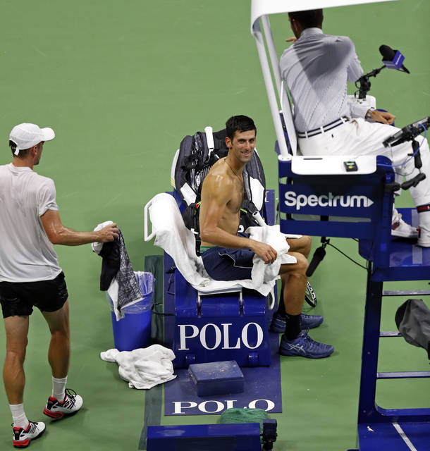 Novak Djokovic, of Serbia, smiles as John Millman, of Australia, goes to change clothes during the quarterfinals of the U.S. Open tennis tournament Wednesday, Sept. 5, 2018, in New York. (AP Photo/Adam Hunger)
