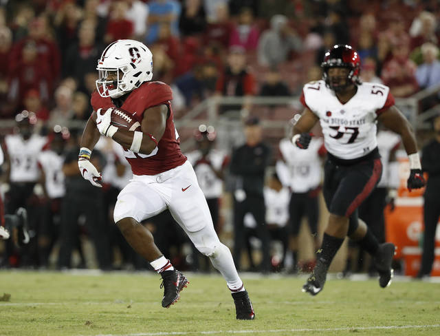 FILE - In this Aug. 31, 2018, file photo, Stanford running back Bryce Love (20) runs for a first down against San Diego State during the second half of an NCAA college football game in Stanford, Calif. Love was held to 29 yards and 18 carries last week against San Diego State. (AP Photo/Tony Avelar, File)