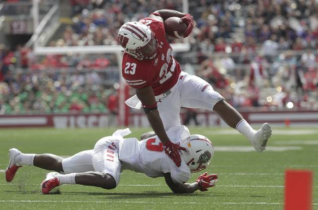 Wisconsin's Jonathan Taylor runs over New Mexico's Michael Sewell Jr. during the second half of an NCAA college football game Saturday, Sept. 8, 2018, in Madison, Wis. Wisconsin won 45-14. (AP Photo/Morry Gash)