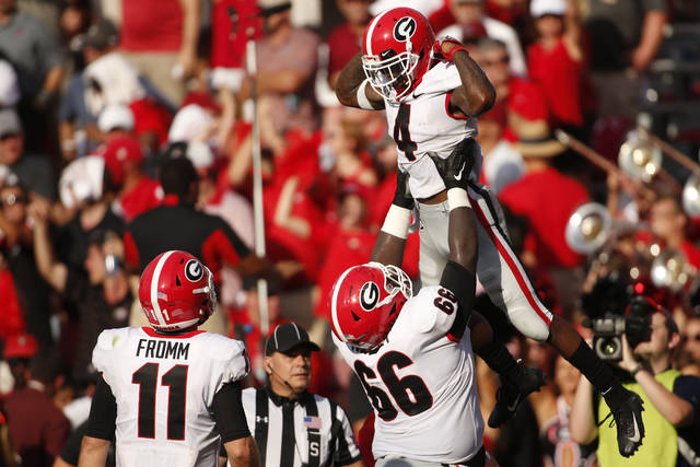 Georgia wide receiver Mecole Hardman (4) celebrates with offensive lineman Solomon Kindley (66) after scoring a touchdown against South Carolina during the second half of an NCAA college football game Saturday, Sept. 8, 2018, in Columbia, S.C. (Joshua L. Jones/Athens Banner-Herald via AP)