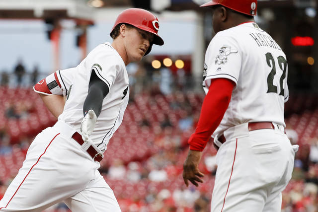 Cincinnati Reds' Brandon Dixon, left, celebrates with third base coach Billy Hatcher (22) after hitting a solo home run off Los Angeles Dodgers starting pitcher Hyun-Jin Ryu in the second inning of a baseball game, Tuesday, Sept. 11, 2018, in Cincinnati. (AP Photo/John Minchillo)