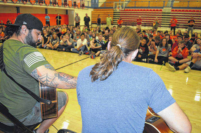 """In the foreground from left are Marine Corps veteran Sal Gonzales and singer and U.S. Navy veteran Jason Michael Carroll. Both of them performed a song for an assembly of the eighth-grade class at Wilmington Middle School. The veterans shared wisdom with the young students, including a comment that """"everybody here will have trauma in this life."""""""