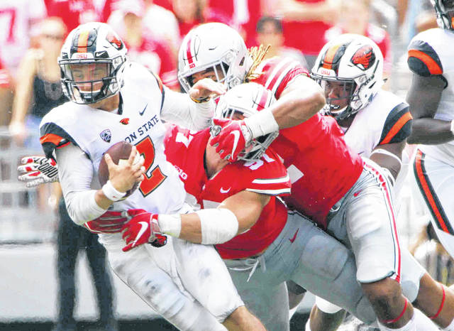 Ohio State defensive linemen Chase Young (2) and Nick Bosa (97) meet at the quarterback on a sack of Oregon State's Conor Blount last Saturday in Ohio Stadium.