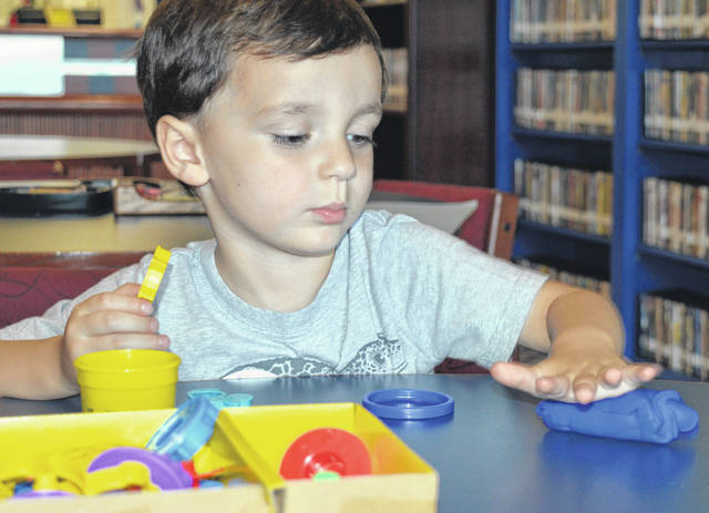 """Cameron DeMange, who just turned 4, enjoys rolling out blue Play-Doh before making animal figures from it by pressing patterns into the modeling compound. Prior to the activity Tuesday, he listened to Clinton-Massie Branch Library Director Kat McKay present two illustrated children's books, """"Dave the Potter: Artist, Poet, Slave"""" and """"Colorful Dreams: The Story of Artist Henri Matisse"""". Story time for all ages is held weekly on Tuesdays at 11 a.m. in the branch library on Lebanon Road."""